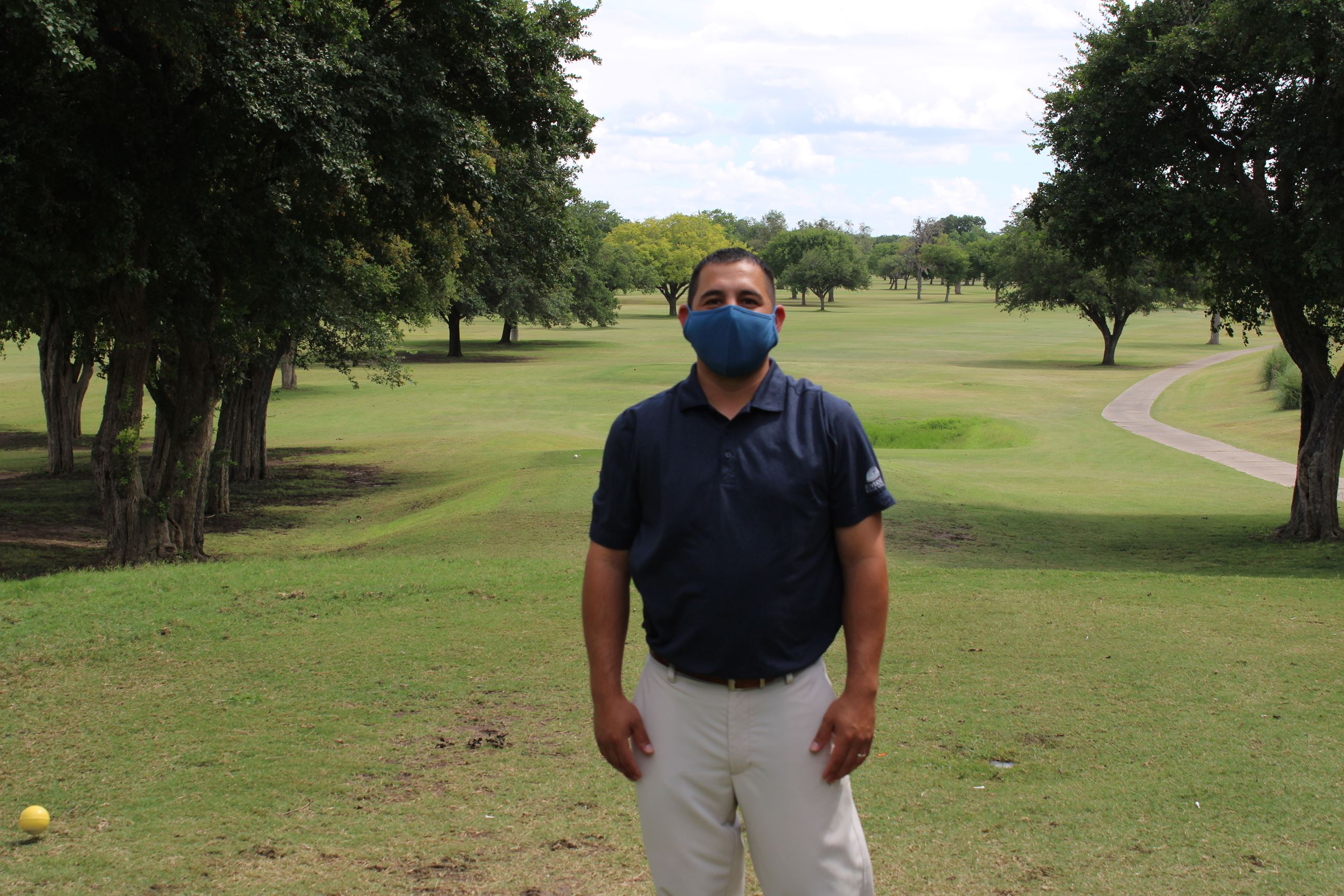 Head Golf Professional Rolando Hernandez wears a face mask at Riverside Golf Course