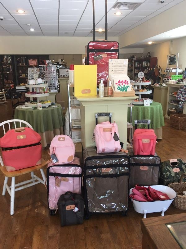 Small display shelving with various purses and bags that are various colors.