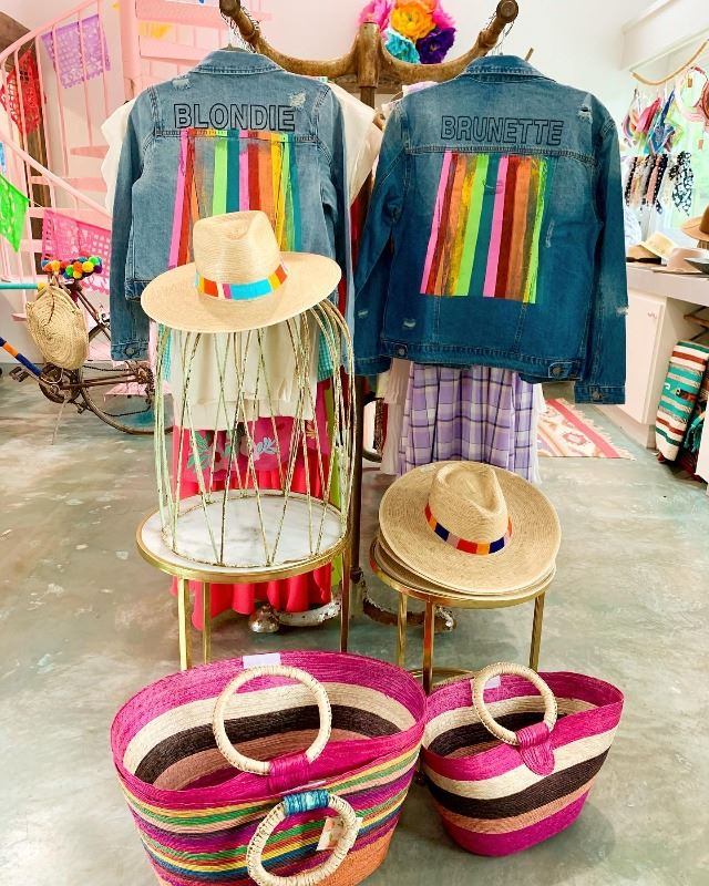 A display of a white skirt, graphic T and hat.