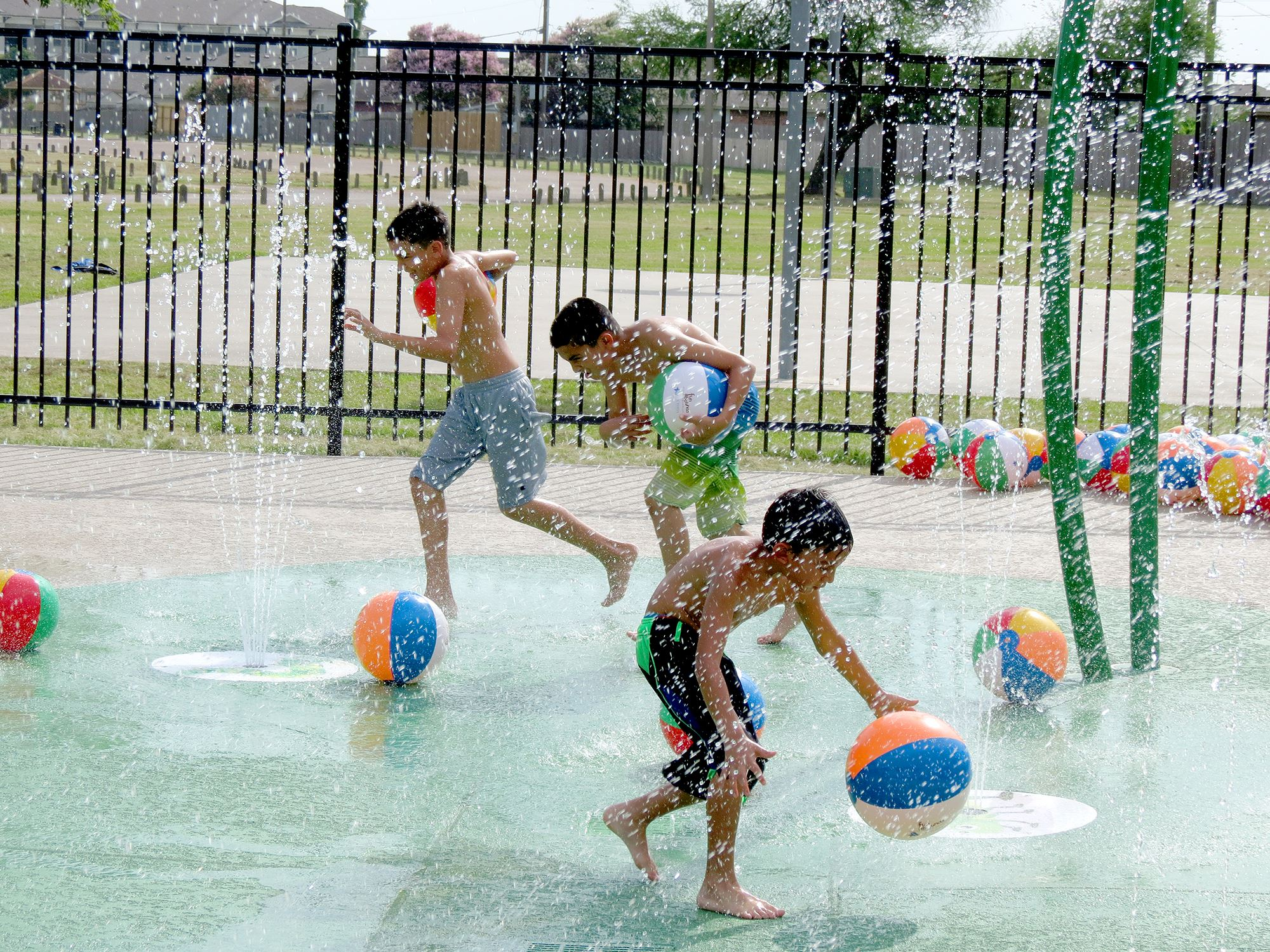 Children play at the Ethel Lee Tracy Park Splash Pad during the facility's 2018 grand opening.