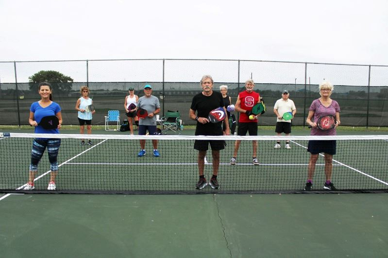 Pickleball players stand at a distance from each other on a pickleball court.