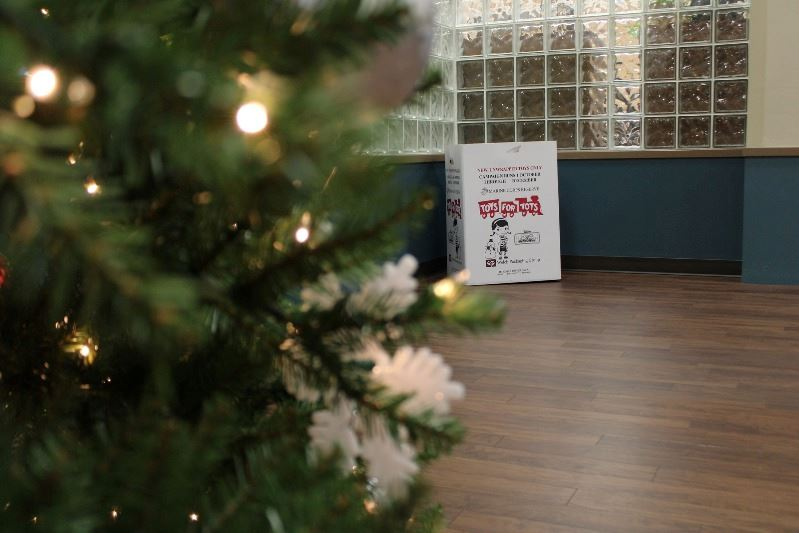 A Toys for Tots donation box sits in the hallway with a Christmas tree in the left foreground.