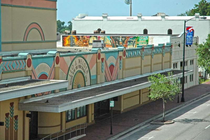 Elevated view of the Leo J. Welder Center building. A Main Street banner and street art are visible.