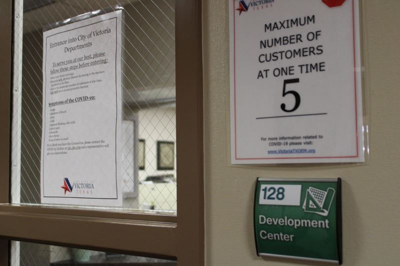 Exterior of the Development Services office with a sign indicating the maximum occupancy is 5 people