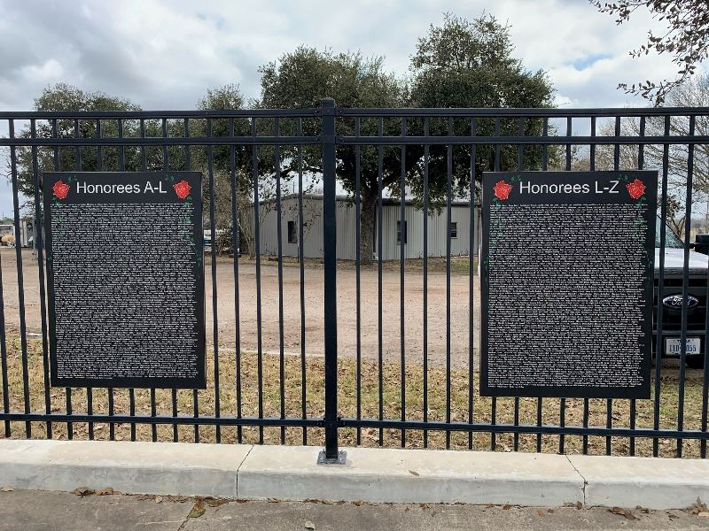 Two large plaques hanging on a black metal fence
