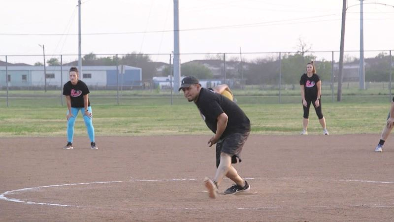 A man prepares to throw a kickball. Two female players stand in the background.