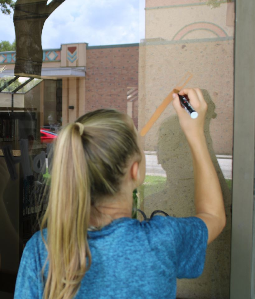 Young girl paints on library window with paint marker