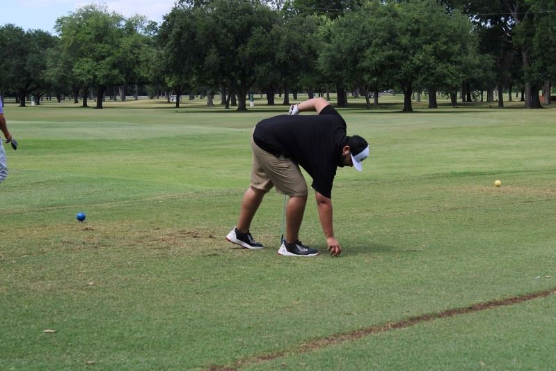 Man placing golf ball on tee at golf course