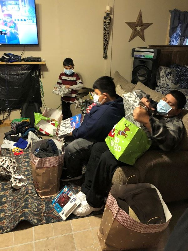 Three boys wearing face coverings open wrapped and bagged Christmas gifts in a living room.