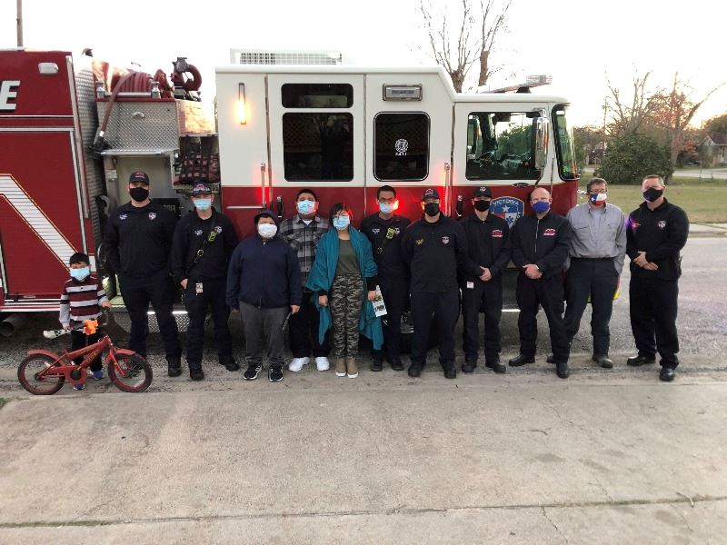Firefighters and residents, including a young boy with a bike, pose in front of a fire engine.