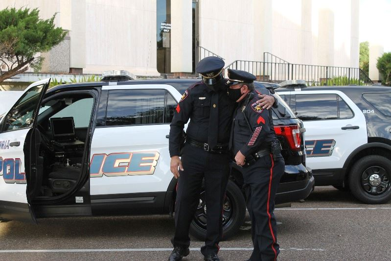 Two masked police officers stand near squad car in parking lot