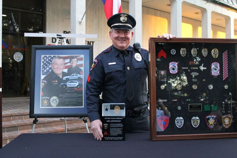 Sergeant Lee Lemmons holds a shadow box at an outdoor ceremony