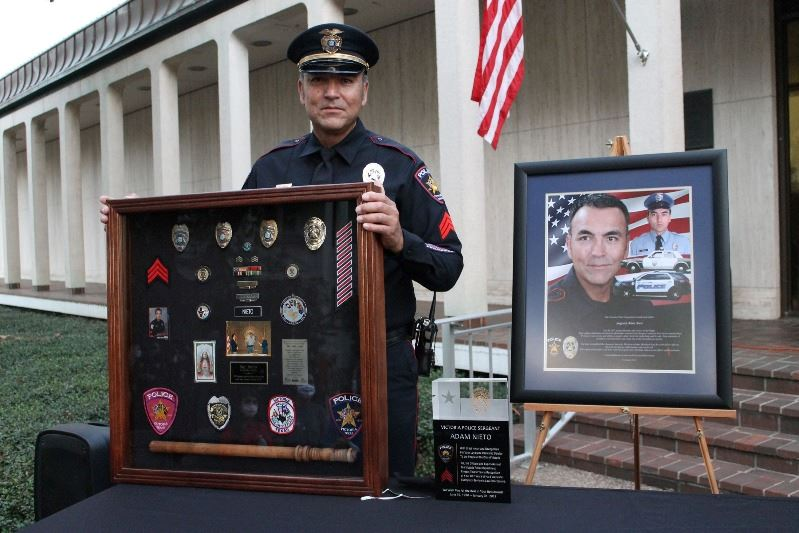 Sergeant Adam Nieto holds a shadow box at an outdoor retirement ceremony.