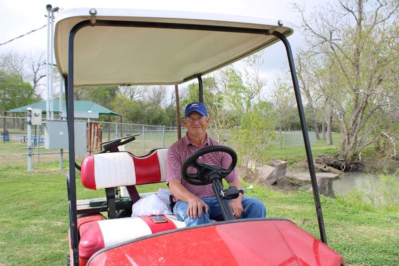 Man in a ball cap sits in a red  Gator-style ATV on a golf course.